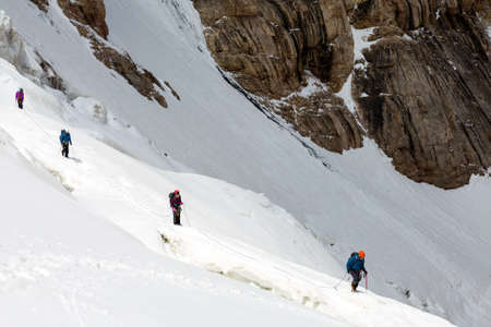 crevasse: Members of Mountain Expedition Walking Along Dangerous Ice Crevasse on Steep Snowfield Rock Wall on Background