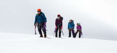 snow climbing: Four People Staying on Mountain High Altitude Snowfield Sporty Clothing and Safety Climbing Gear Mature Male Guide and Young Female Athletes Stock Photo