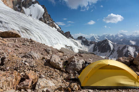 bivouac: Mountain View with Ice Glacier and Peaks on Background and Small Single Alpine Yellow Tent located on Rocky Moraine on Foreground