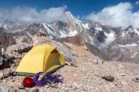 casco rojo: Amarillo pequeña tienda de material de escalada cuerda Piqueta Casco Rojo Rocky Wild Terrain majestuoso pico rango de vista del cielo azul de las nubes