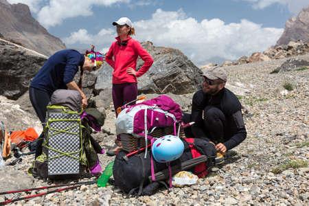 Gruppe von Personen, Mann und Frau sitzen Bleiben Sie zusammen mit großen Taschen mit Kletterausrüstung angebaute wie Helm Isomatte Wanderstöcke Eispickel Standard-Bild