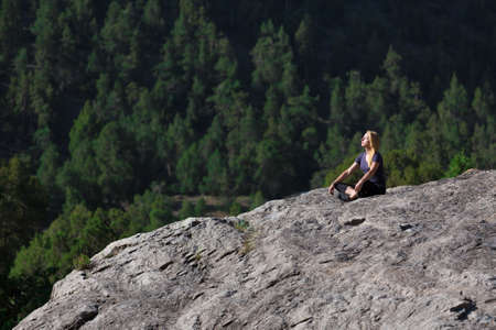 finesse: Attractive Female Athlete Sitting in Yoga Mediation Pose on Grey Rock Mountain Green Forest on Background