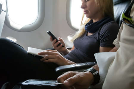 Casual Clothing Woman in Plane Seat Browsing Her Smart Phone and Holding Documents for Immigration Formalities Hand of Man on Foreground Focus on Female Hands Foto de archivo
