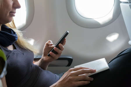 formalities: Casual Clothing Woman in Plane Seat Browsing Her Smart Phone and Holding Documents for Immigration Formalities Illuminators on Background