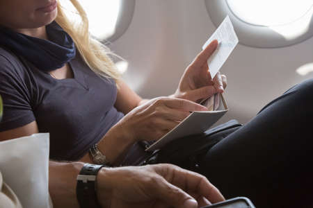 formalities: Casual Clothing Woman in Plane Seat Preparing her Documents for Immigration Formalities Male Hand Holding Telephone on Foreground