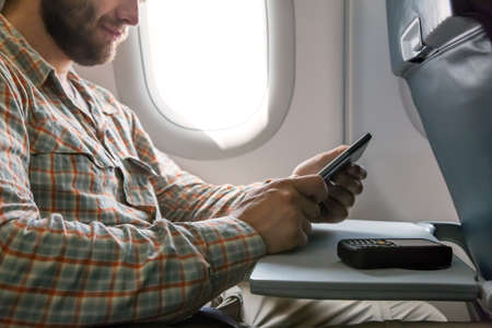 air travel: Person sitting inside airplane Window Seat Using Electronic Gadget Casual Clothing Bearded Stock Photo