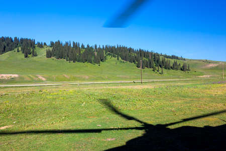 rotor: Rural Area of Green Grassy Kirghiz Steppe and Shadow of Helicopter Rotor Screw Stock Photo