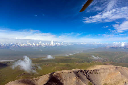 aereal: Central Asia Landscape Areal View from Helicopter Desert Hills on Foreground Grassy Meadows and High Snowbound Mountain Range Blue Sky Clouds
