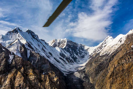 ridges: Aerial View of High Altitude Snowbound Mountains with Massive Glaciers Sharp Rock Ridges and Ice Slopes from Helicopter with Rotating Screw Blade Stock Photo