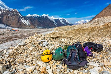 expedition: Mountain Expedition Luggage on Rocky Moraine of Glacier Many Bags and Backpacks Peaks and Blue Sky