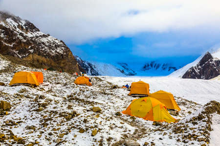 tyan shan mountains: Many Orange Tents Located on Side Rock Moraine of Glacier in Severe Snow and Ice Peaks Valley