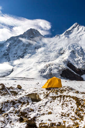 tyan shan mountains: Steep Snowbound Peaks Bivouac Assembled on Rocky Moraine of Glacier Stock Photo
