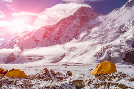 tyan shan mountains: Steep Snowbound Peaks Bivouac Assembled on Rocky Moraine of Glacier Sun Shining Stock Photo