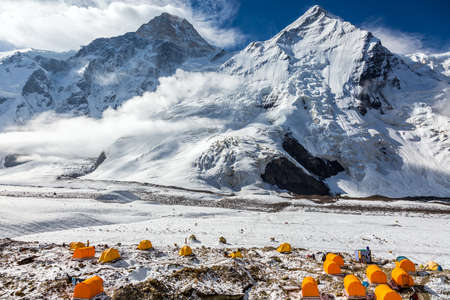 tyan shan mountains: Many Orange Tents Located on Side Rock Moraine of Glacier in Severe Snow and Ice Peaks Landscape