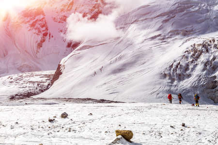 tyan shan mountains: Massive Glacier at High Altitude Severe Mountains and Small Body of Alpine Climber with Backpack and Trekking Poles Walking on Ice  Clouds Moving Down