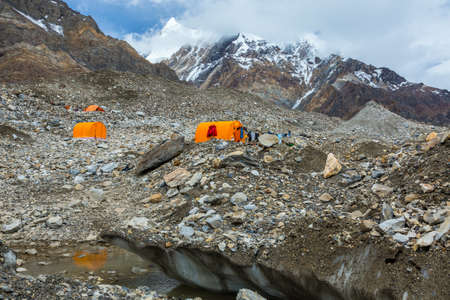 crevasse: Mountain Expedition Camp Located on Glacier Moraine with Large Ice Crevasse and Melting Lake on Foreground Clothing Hanged on Tent for Drying after Rain