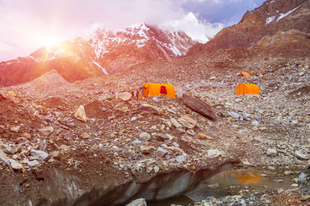 crevasse: Mountain Expedition Camp on Glacier Moraine with Large Ice Crevasse and Melting Lake Foreground Clothing Hanged on Tent for Drying after Rain Sun Shining Stock Photo