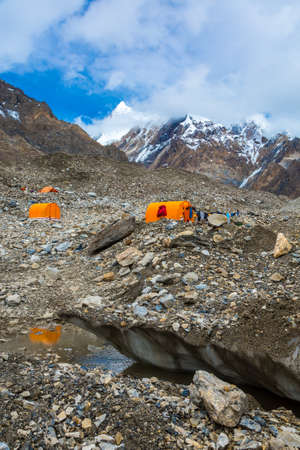 crevasse: Mountain Expedition Camp on Glacier Moraine with Large Ice Crevasse and Melting Lake Foreground Clothing Hanged on Tent for Drying after Rain