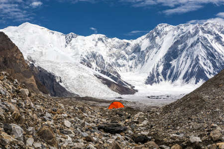 bivouac: One Red Camping Tent Located on Rock Moraine of Giant Glacier in High Altitude Mountains with Peak Range Summits on Background Sun Blue Sky Clouds