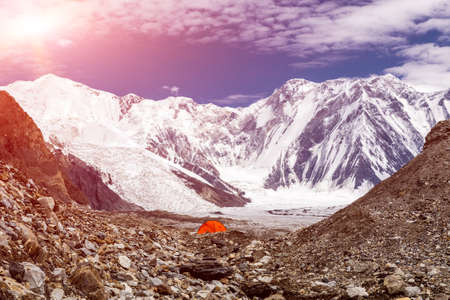 tyan shan mountains: One Red Camping Tent Located on Rock Moraine of Giant Glacier in High Altitude Mountains with Peak Range Summits on Background Sun Blue Sky Clouds