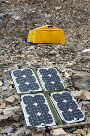 tyan shan mountains: Solar Battery on Rocky Glacier Moraine for Electricity Supply of Sport Mountain Expedition in Wilderness Country with Large Yellow Tent on Background