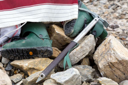 ice axe: Composition of Mountain Climbing Footwear and Gear in Stones Green Plastic High Altitude Old Boots and Vintage Style Ice Axe