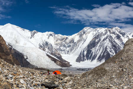 tyan shan mountains: Panorama of High Mountains Range and Red Camping Tent on Glacier Moraine with Female Hiker Silhouette Aside Stock Photo