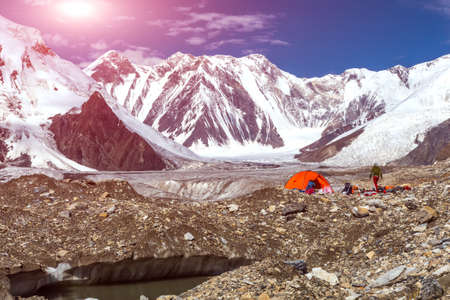 tyan shan mountains: Glacier Crevasse with Melting Water Lake Red Camping Tent Female Hiker and Mountain Panorama with Clean Sky and Shining Sun