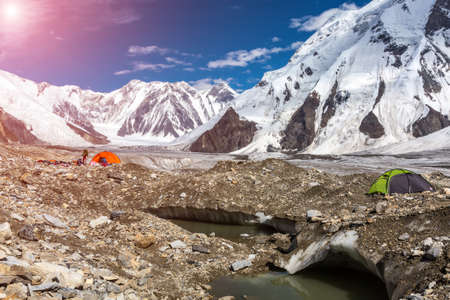 crevasse: Panorama of High Mountains Range with Red and Green Tents on Glacier Moraine and Shining Sun Ice Crevasse and Lake on Foreground