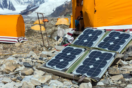 Solar Battery on Rocky Glacier Moraine for Electricity Supply of Sport Mountain Expedition in Wilderness Country with Camping Tents on Background Stockfoto