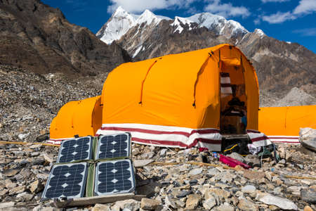 tyan shan mountains: Solar Battery on Rocky Glacier Moraine for Electricity Supply of Sport Mountain Expedition in Wilderness Country with Camping Tents on Background Stock Photo