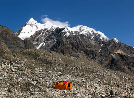 tyan shan mountains: Base Camp of High Altitude Expedition at Mountains with Snow and Ice Summit Orange Bivouac with Sleeping Bags Drying on Roof of It Stock Photo