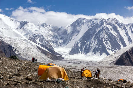Group of Alpine Climbers Working on setting up Camping Tents at Side Rocky Moraine of Glacier and High Altitude Mountain Range on Background Stock Photo