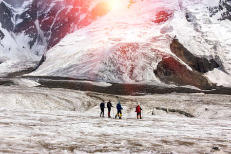 ascent: Group of Mountain Climbers with High Altitude Boots and Clothing Crossing Ice Section During Ascent of Alpine Expedition in Asia Mountain Area Sun Shining