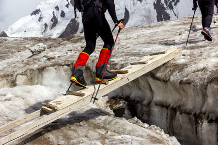 ascent: Group of Mountain Climbers with High Altitude Boots and Clothing Crossing Ice Section During Ascent of Alpine Expedition in Asia Mountain Area