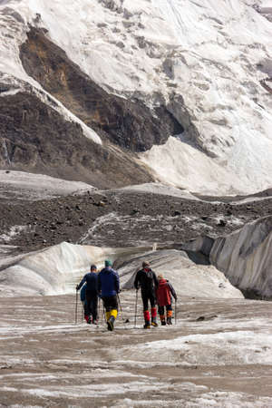 ascent: Group of Mountain Climbers with High Altitude Boots and Clothing Crossing Ice Section During Ascent of Alpine Expedition in Asia Mountain Area Vertical