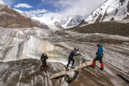 crevasse: Group of Mountain Climbers with High Altitude Boots and Clothing Crossing Ice Section During Ascent of Alpine Expedition in Asia Mountain Area