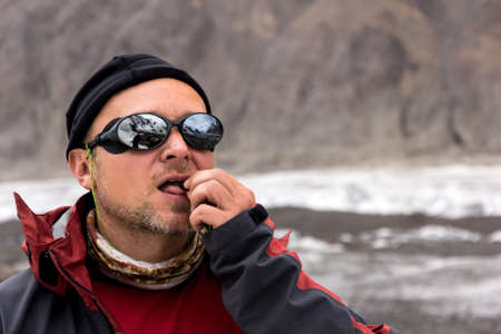 man nuts: Face of Man Serious Face Sporty Clothing Protective Sunglasses Eating Nuts with Mountain Peaks Reflection Stock Photo