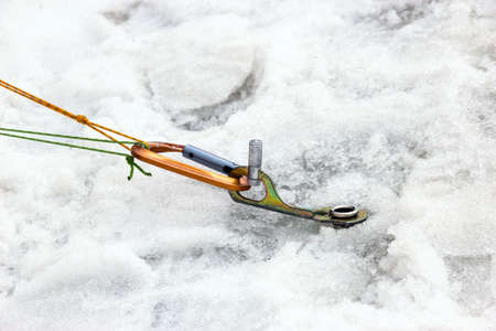 screwed: Ice Piton Screwed into Ice with Belaying Ropes and Carabiner Safety Mountain Climbing Gear Used on Glacier Snow Close Up