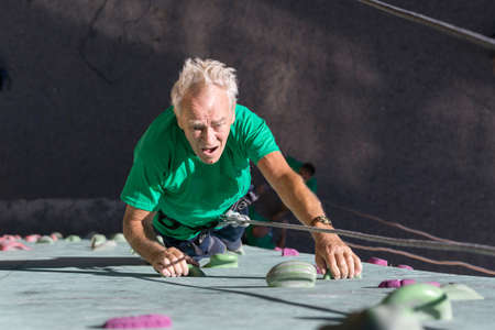 belaying: Elderly Male Climber Makes Hard Move on Outdoor Climbing Wall Sporty Clothing on Fitness Training Course Intense but Positive Face Using Rope and Belaying Gear
