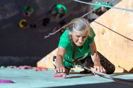 Elderly Female Demonstrates Excellent Physical and Mental Abilities Ascending Vertical Climbing Wall Group of Climbers Staying Below on Ground