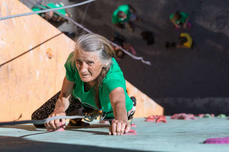 belaying: Elderly Female Makes Hard Move on Outdoor Climbing Wall Sporty Clothing on Fitness Training Intense but Positive Face Using Rope and Belaying Gear