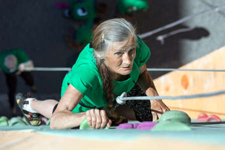 belaying: Elderly Female Moving Up on Outdoor Climbing Wall Sporty Clothing on Fitness Training Intense but Positive Face Using Rope and Belaying Gear