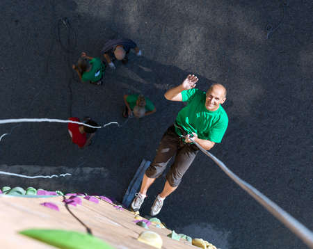 belaying: Positive Mature Extreme Climber Greeting Waving Hand Hanging High on Belaying Rope on Outdoor Rock Climb Gym