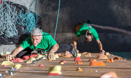 80s adult: Elderly Female Moving Up on Outdoor Climbing Wall Sporty Clothing on Fitness Training Intense but Positive Face another Climber Start His Ascent on Background