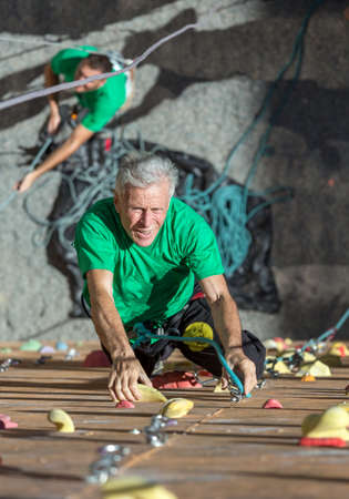 belaying: Portrait of Handsome Adult Male Climber Moving Up on Sport Training Course in Outdoor Climb Gym Using Rope and His Belaying Partner on Background