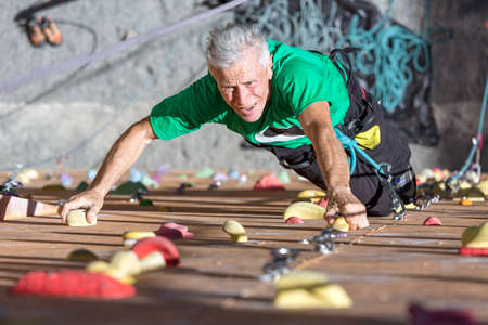 Portrait of Mature Male Climber Moving Up on Outdoor Climbing Wall Sporty Clothing on Fitness Training Intense but Positive Face Using Rope and Belaying Gear Standard-Bild