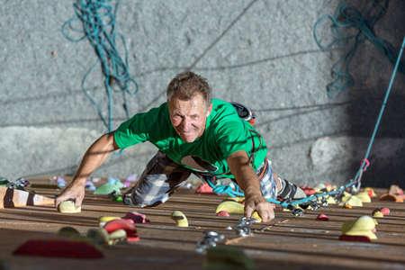 hombres maduros: Retrato de guapo del varón adulto Escalador Moverse hacia arriba sobre el deporte curso de formación en la subida al aire libre Gimnasio Uso de Cuerda Nudos de engranajes con Emoción positiva Cara Inspirado Foto de archivo