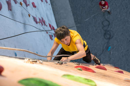 belaying: Elderly Female Demonstrates Excellent Physical and Mental Abilities Ascending Vertical Climbing Wall Belaying Partner Staying Below on Remote Ground Stock Photo