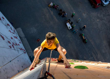 high up: Elderly Female Climber Makes Hard Move and Looking High Up on Outdoor Climbing Wall Sport Competitions Very Emotional Face Belaying Partner Fans Staying Remote Ground Stock Photo